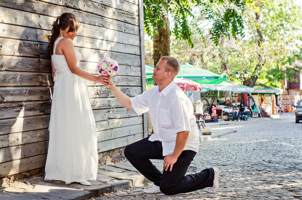 Groom kneeling in front of the bride
