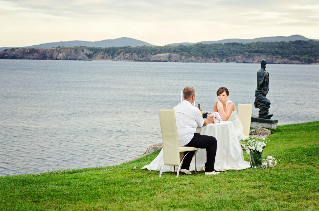 Roamntic photo of wedding couple on a table near the sea
