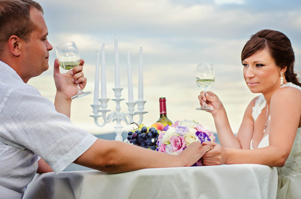 Bride and groom holding hands and glasses of wine