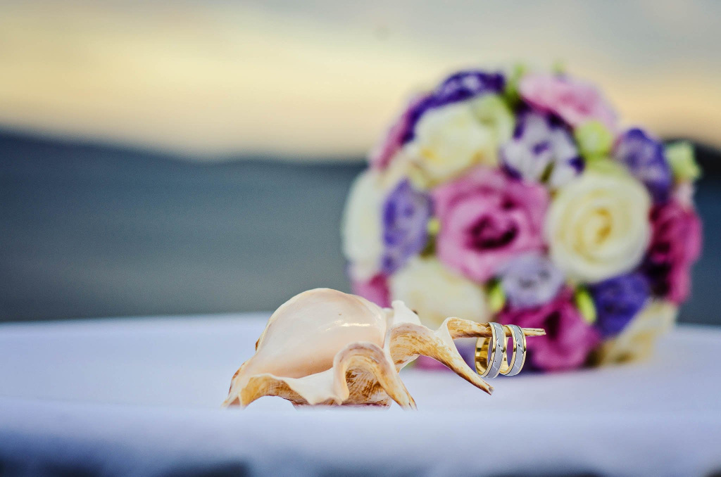 Wedding rings on a seashell and the wedding bouquet