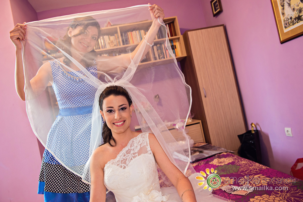 Friend holding the veil of the bride