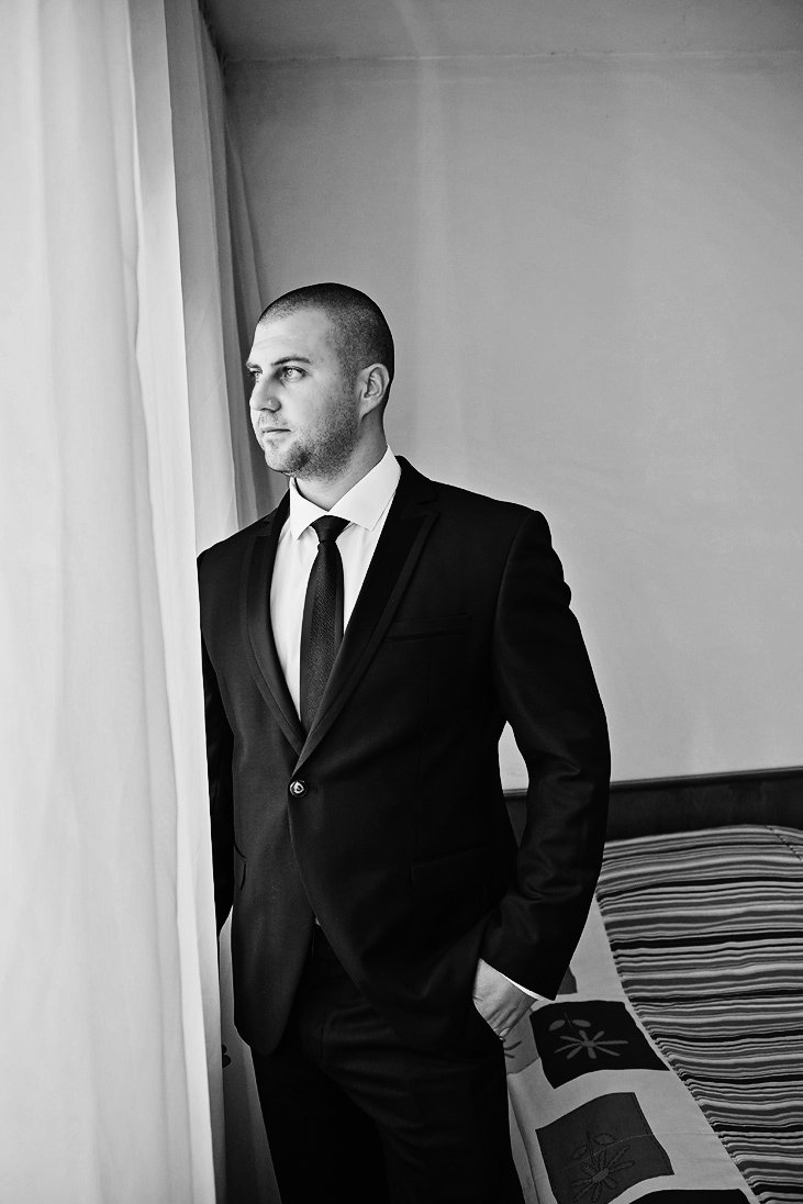 Black and white photo of a groom standing