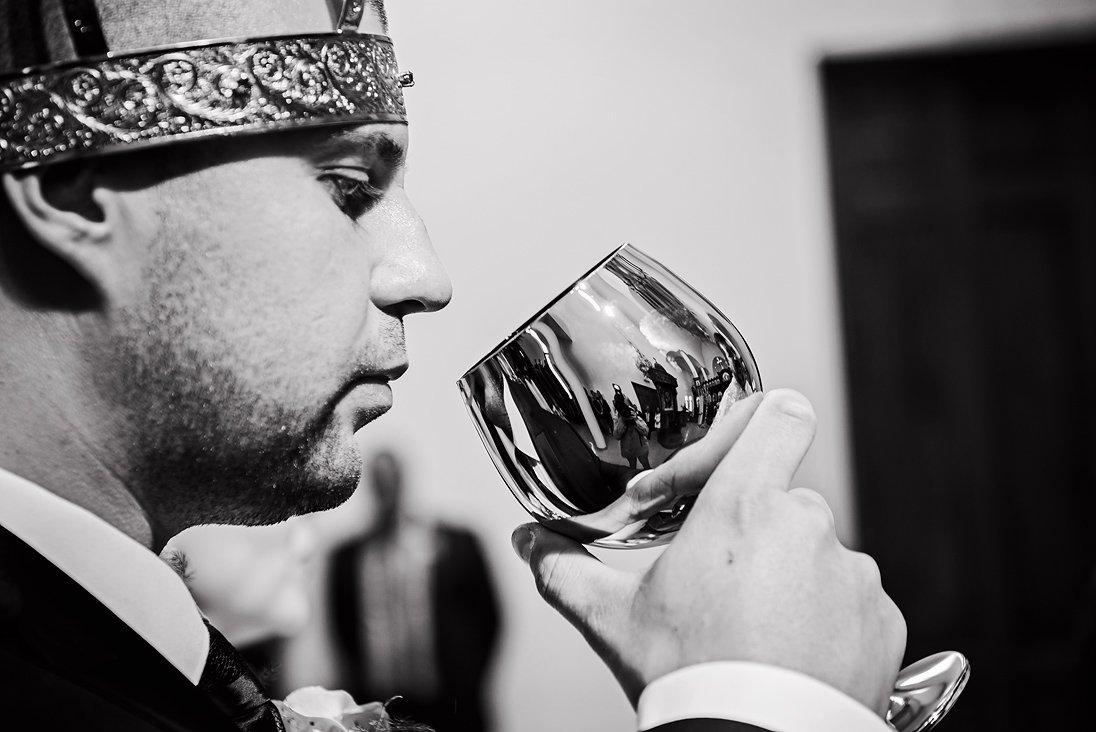 The groom and the ritual wedding glass