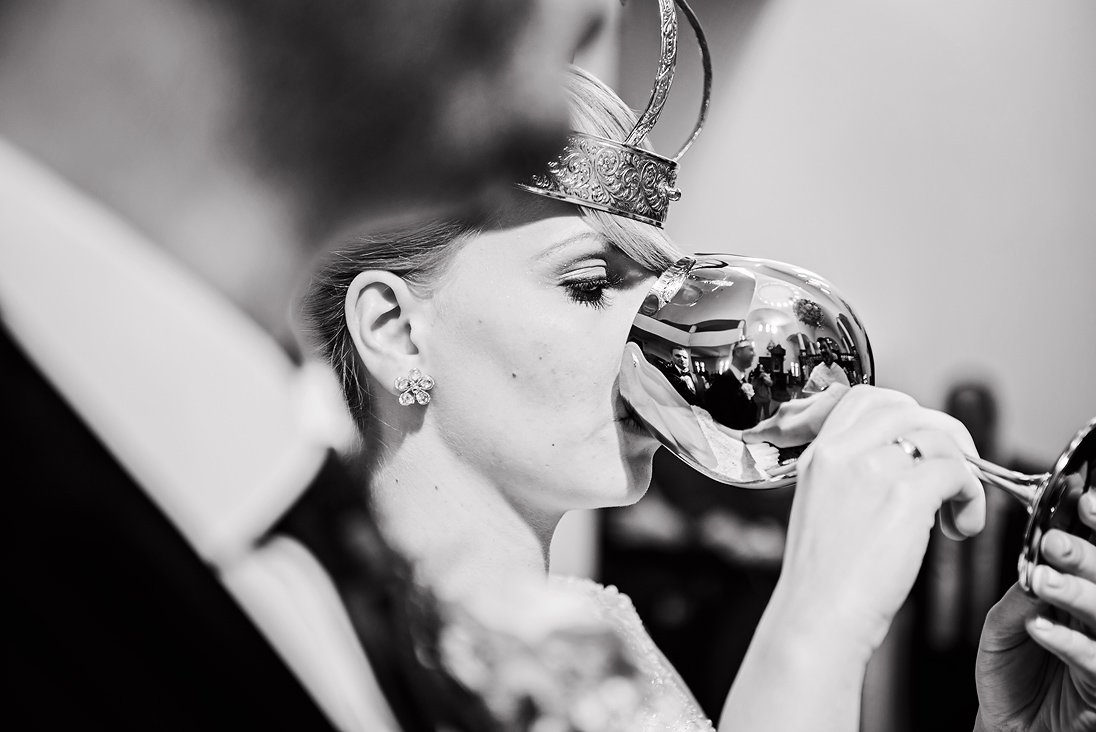 Bride in church drinking from the holy glass