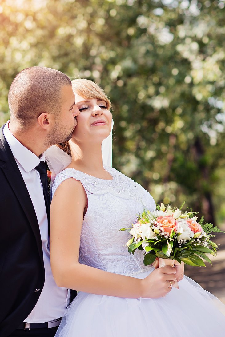 Groom kissing the bride who is holding the wedding bouquet