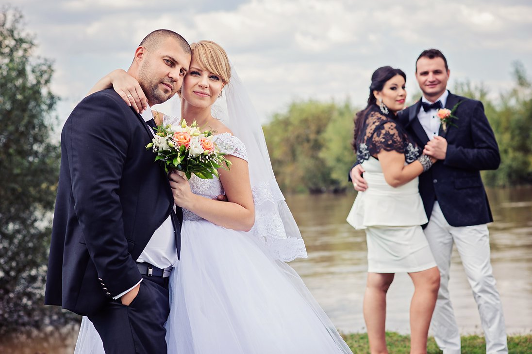Wedding couple and friends by a lake