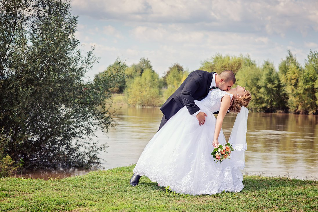 Groom kissing the bride by a lake