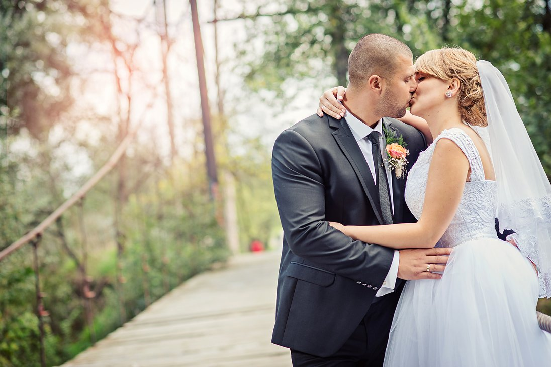 Bride kissing the groom on a wooden bridge