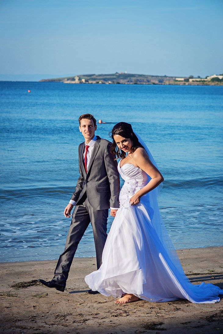 Bride and groom walking by the sea in Santa Marina, Bulgaria