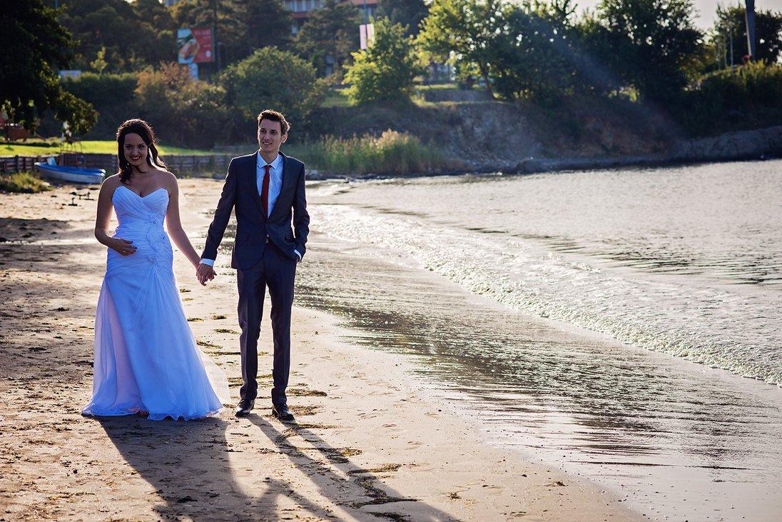 The sun shines on the wedding couple near the sea
