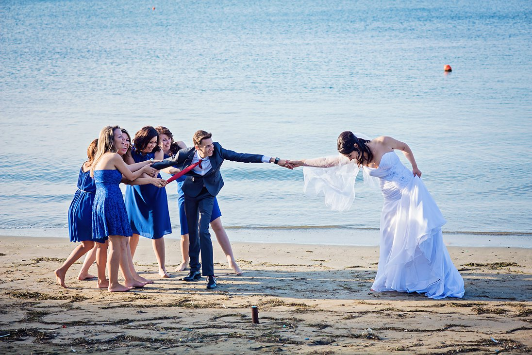 Funny wedding photosession groom, bride and maids of honor by the sea