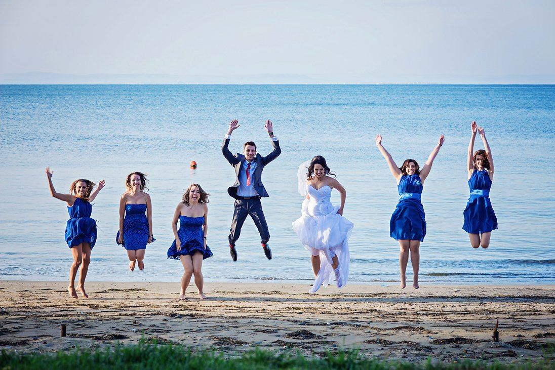 Bride, groom and maids of honor jumping by the sea