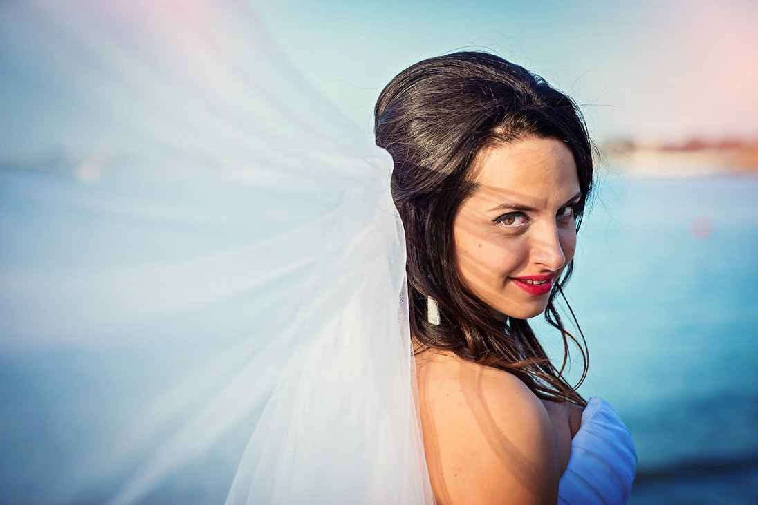 Bridal portrait with a veil by the sea
