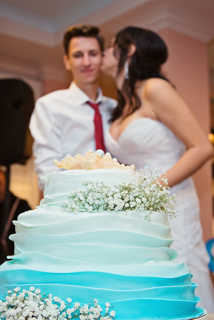 Bride kissing the groom in front of the wedding cake