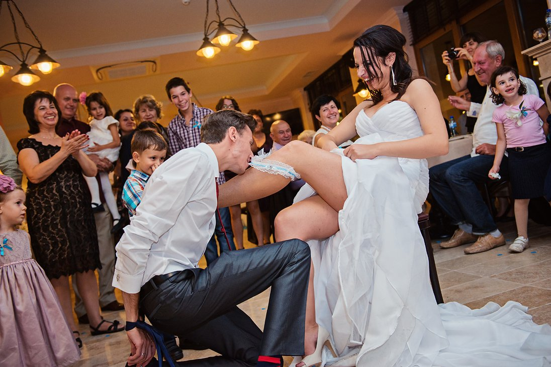 Groom taking the garter off with hands tied