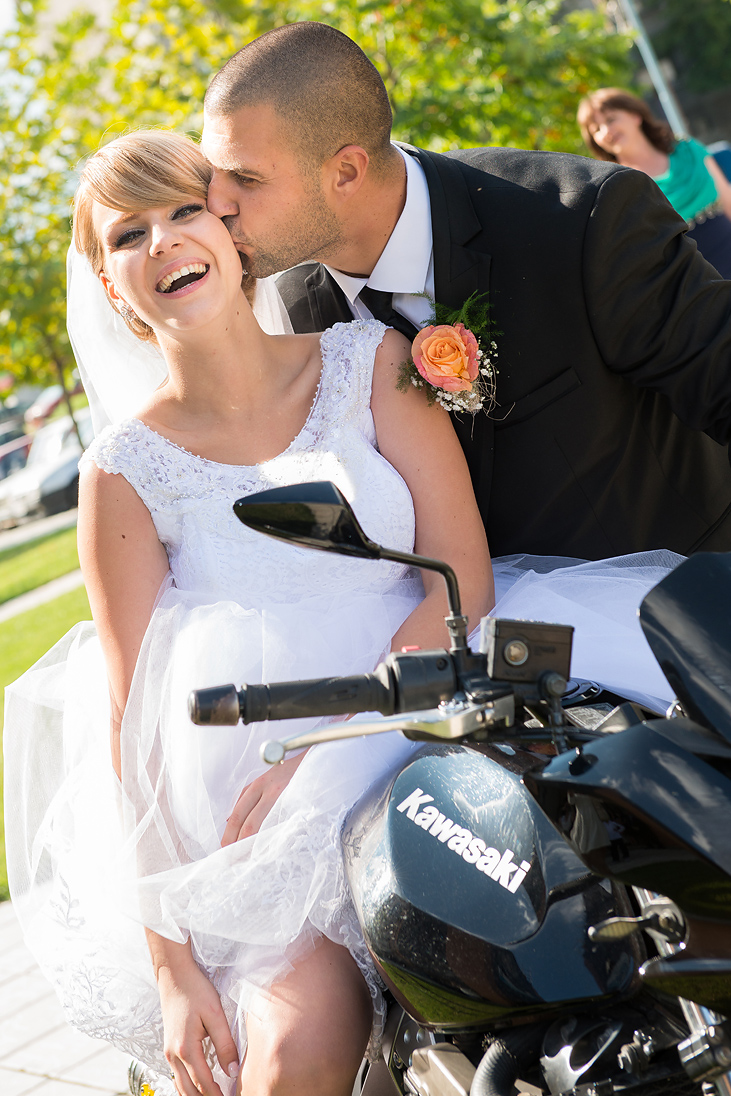 Groom kissing the bride on a motorcycle