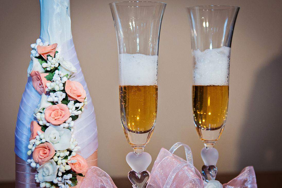 A wedding champagne with roses decoration and glasses