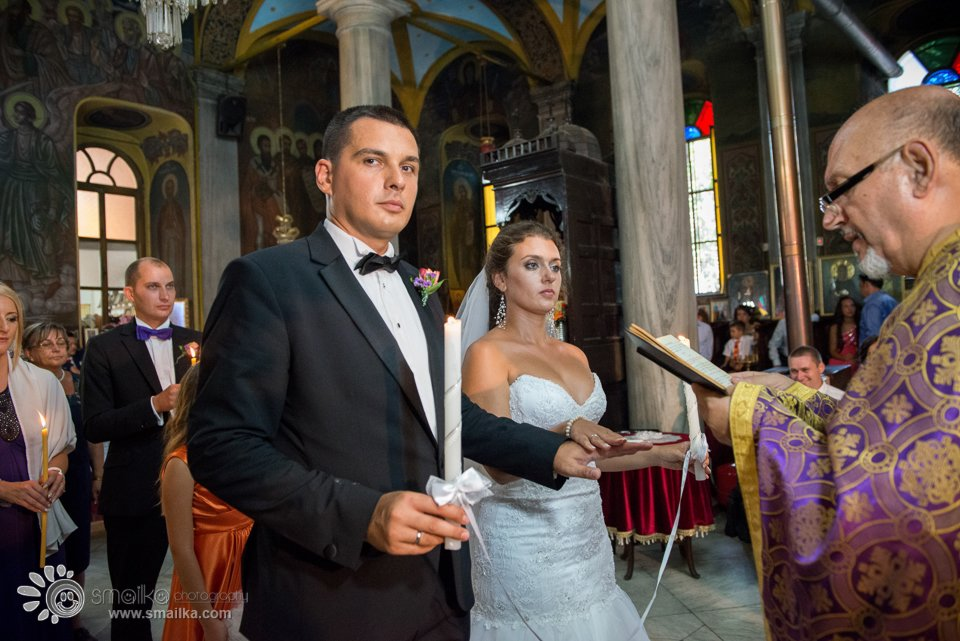 Milena Nikolay church ceremony photo of couple holding hands priest reading