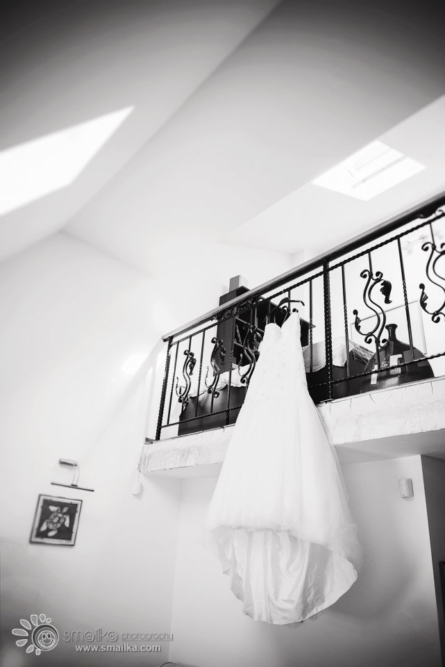 A balck and white photo of a wedding dress hanging