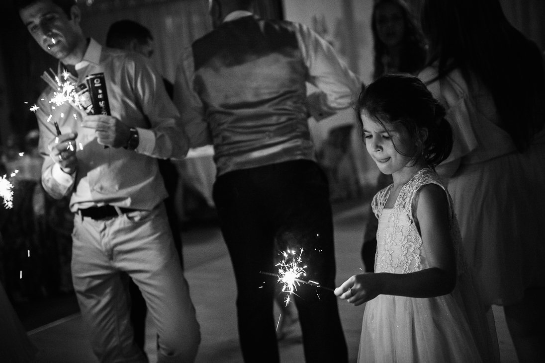 Kid is holding sparkling lights at the wedding