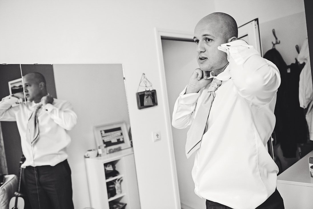 Balck and white photo of a groom putting his tie on