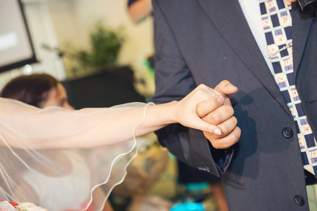 Father is holding the hand of the bride