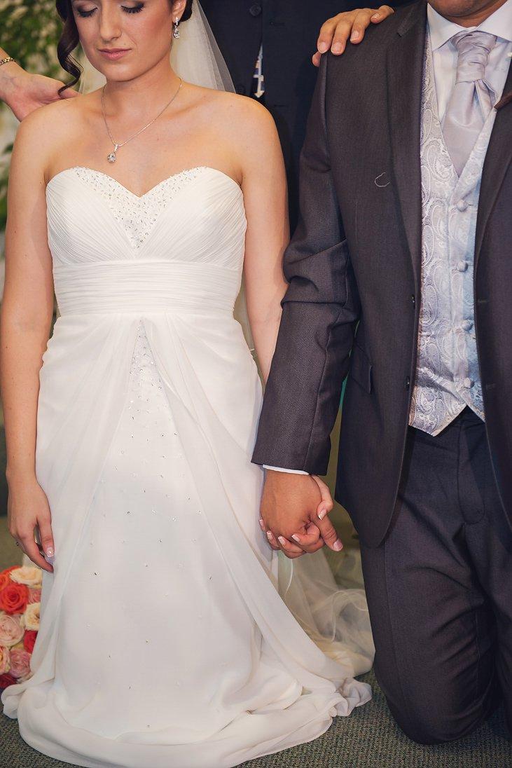 Bride and groom kneeling holding hands