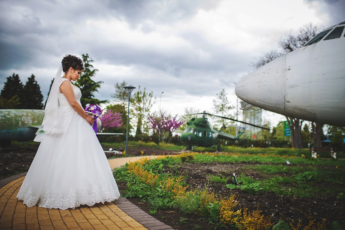 Bride holding a wedding bouquet in front of an airplane