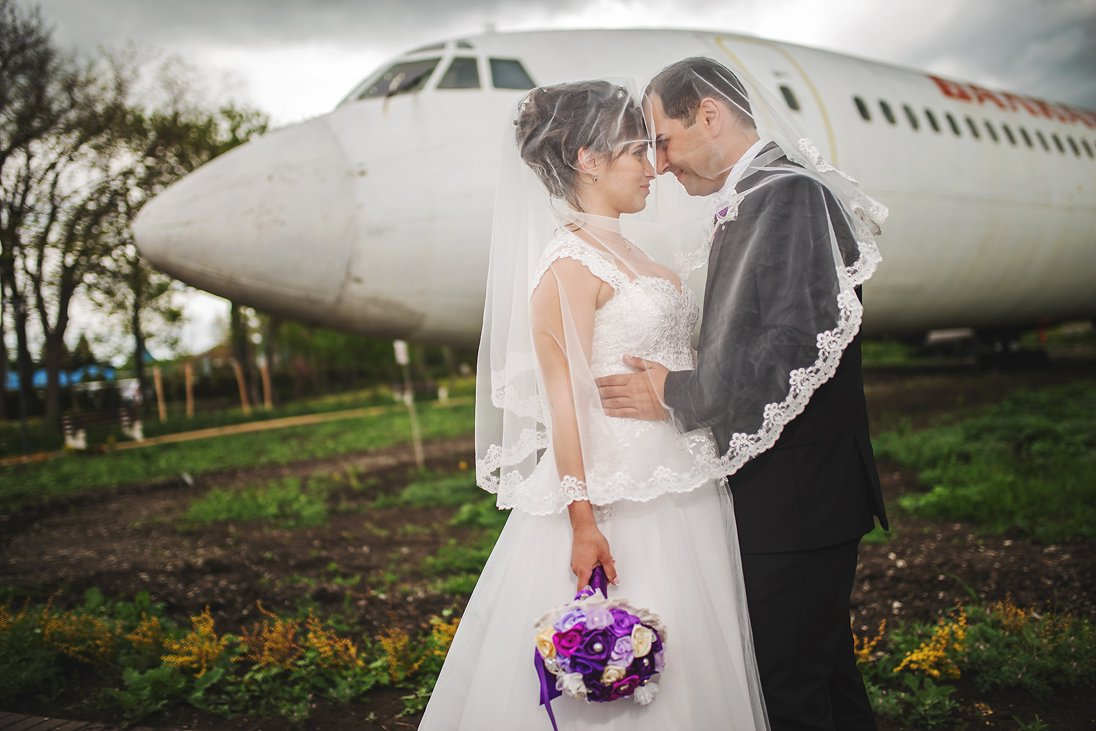Wedding couple under the veil in front of an airplane