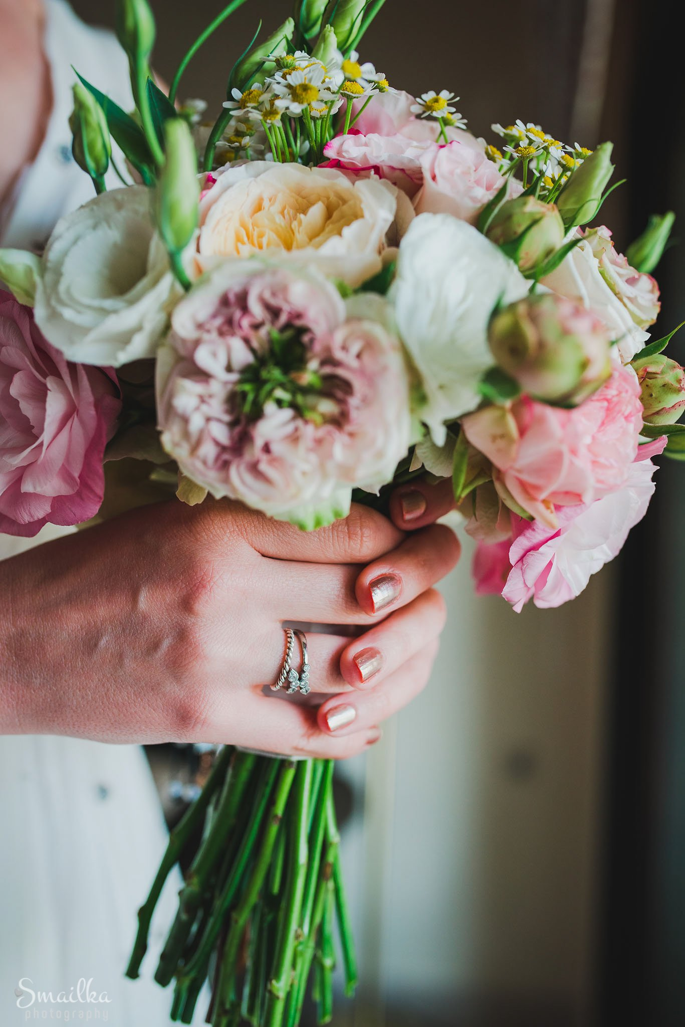 Bride is holding a wedding bouquet of fresh flowers