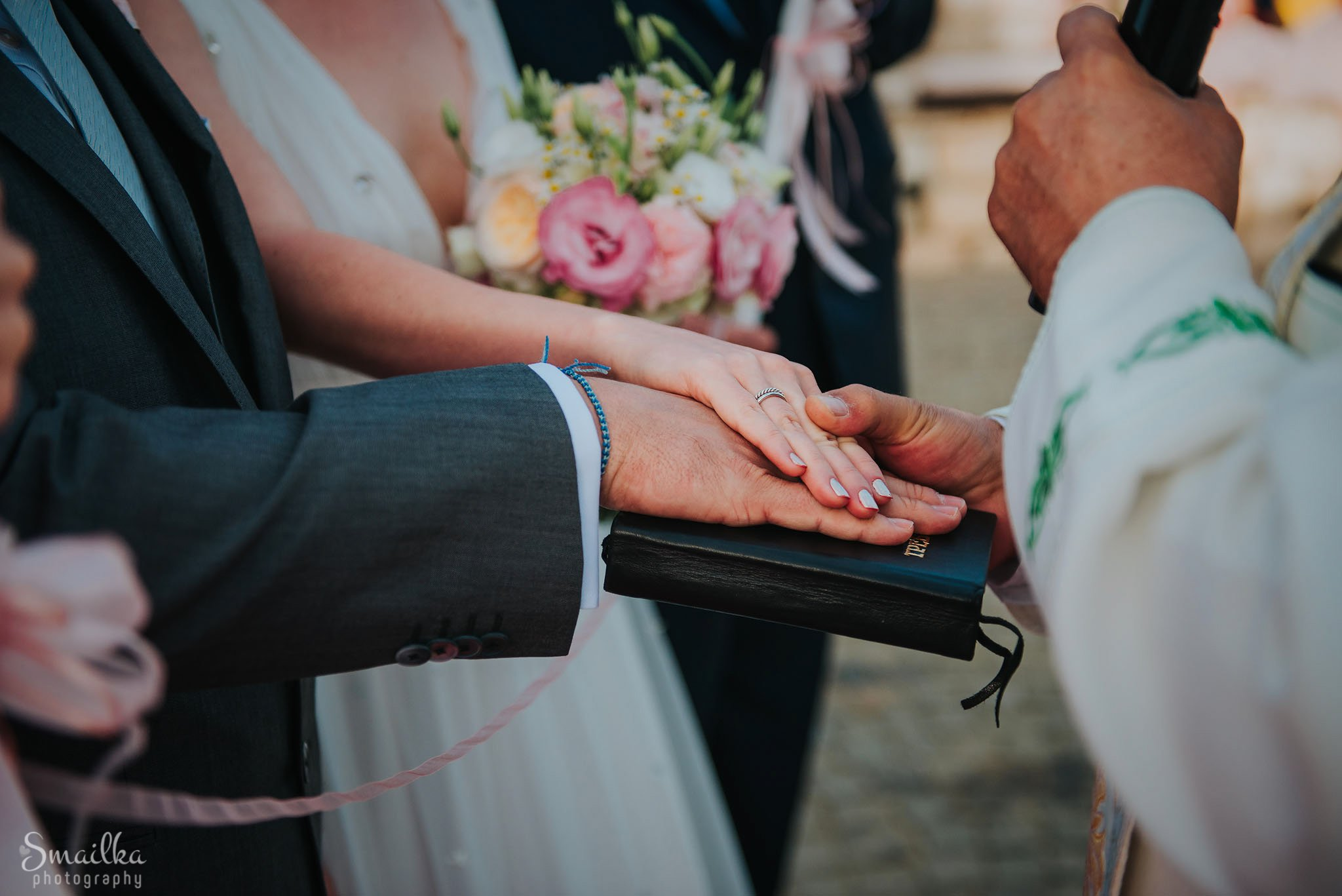 Wedding couple taking a vow hand in hand over the Bible