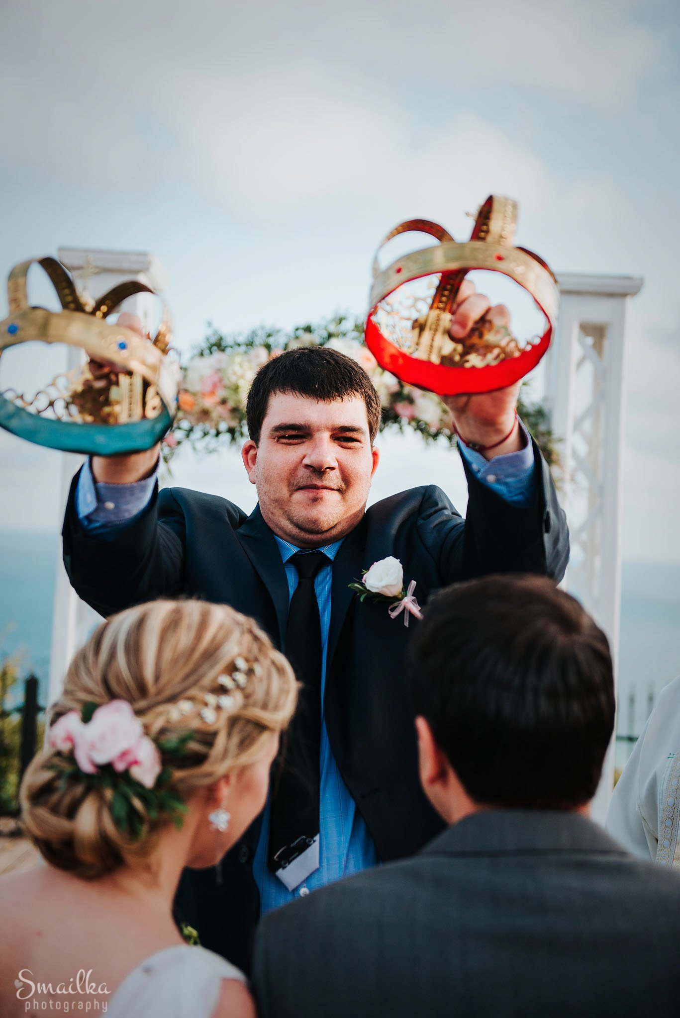 Best man changing wedding crowns over bride and groom