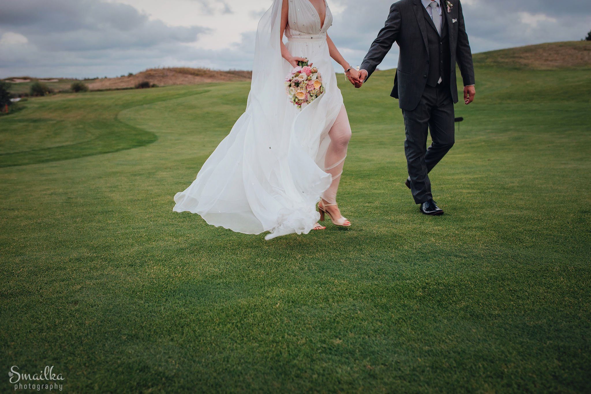 Wedding couple walking the golf green at Black Sea Rama