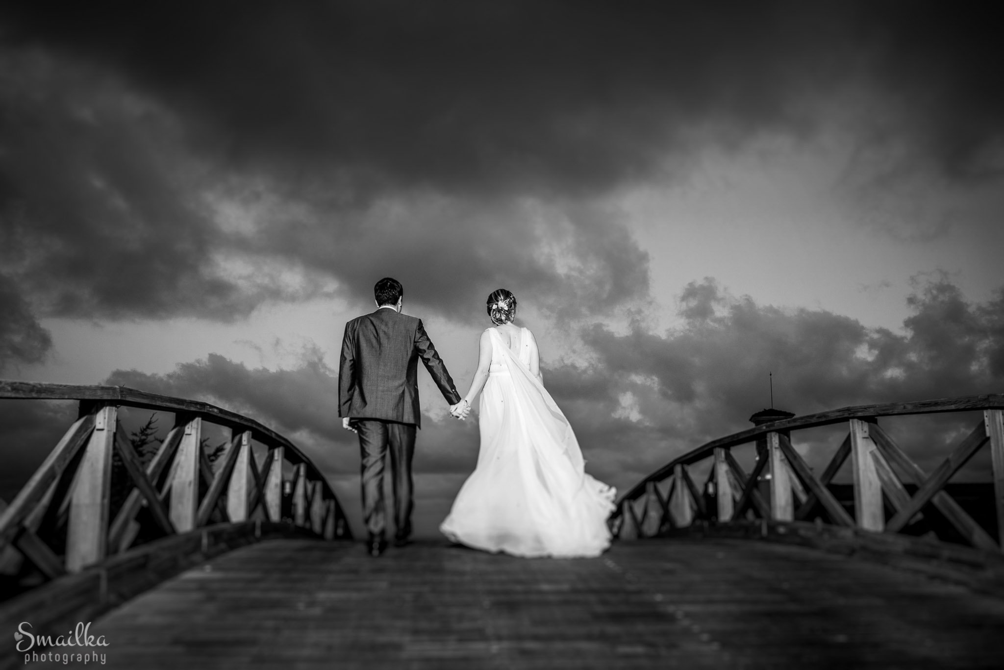 Wedding couple facing dramatic clouds on a bridge at Black Sea Rama